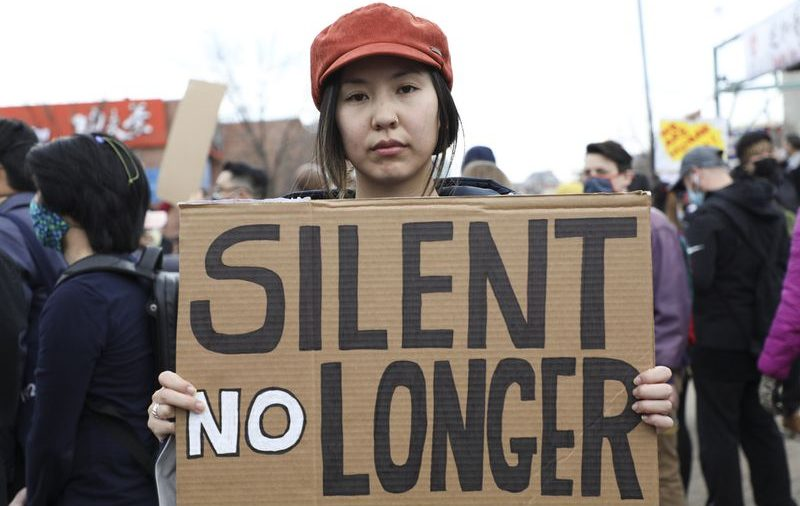 """A woman holds up a sign """"Silent No Longer"""" at a #stopasiainhate protest. Cr: Google Images"""